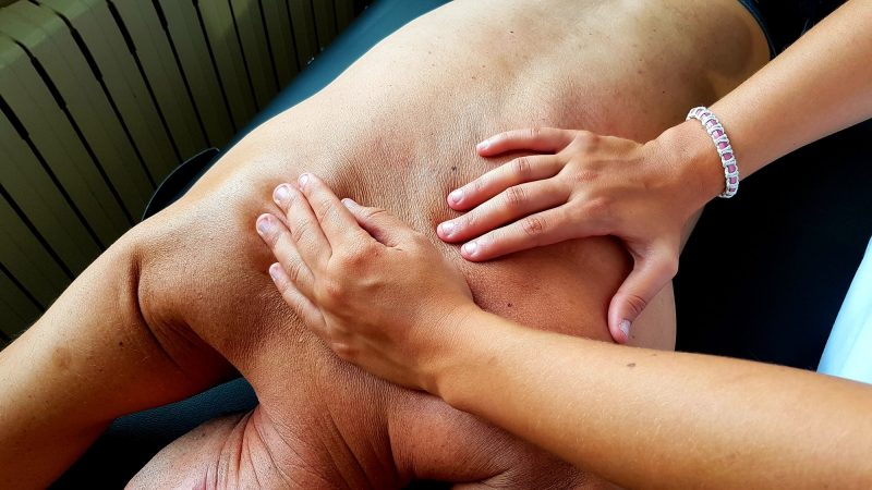 Female physical therapist assinting a male patient giving exercising treatment massaging the back